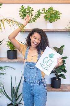 Свобода выбора. эмоциональная молодая женщина-мулатка с веганским плакатом, показывающим жест свободы, стоя в помещении с растениями