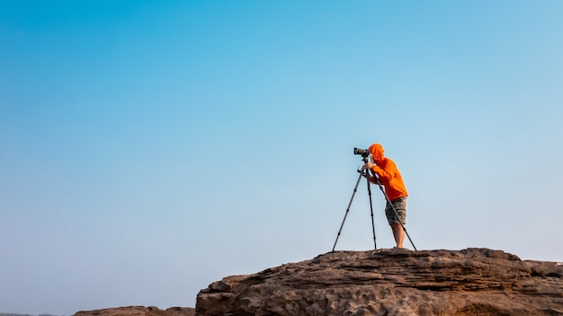 Freedom photography stock images shooting camera tripod on mountain rock at sam phan bok ubon ratchathani thailand isolated blue sky background