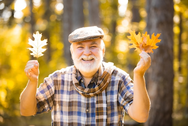 Freedom retirement concept active senior man having fun and playing with the leaves in autumn forest...