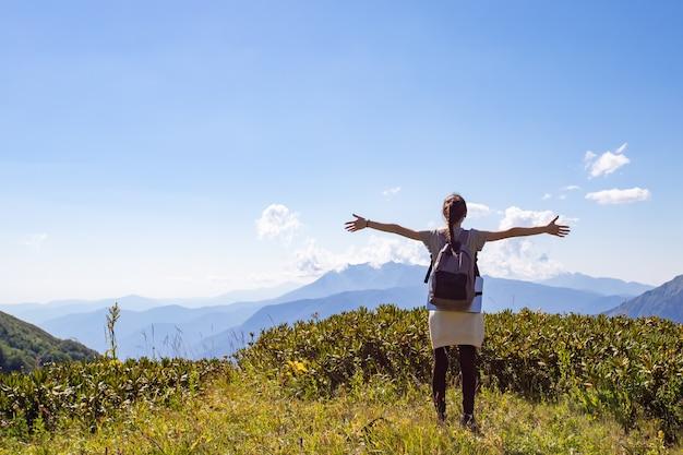 자유, 성공, 행복. 산에 있는 한 소녀가 풍경을 바라보고, 손을 위로 들고, 뒤에서 보이는 풍경을 바라보고 있습니다.