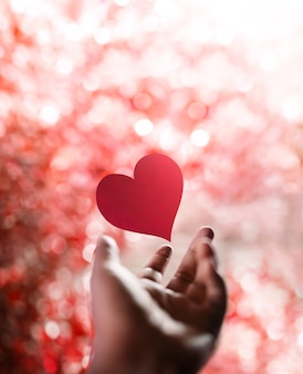 Свобода любви, воображению, психическому здоровью и концепции творчества. красное сердце парит над раскрытой рукой гостьуре. позитивный ум, умиротворение, наслаждение и жизненная философия