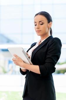 어디에서나 일할 수 있는 자유. 야외에 서 있는 동안 디지털 태블릿에서 작업하는 formalwear에 자신감이 젊은 여자