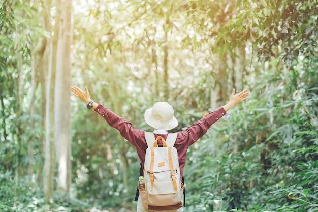 Свобода туристическая путешественница молодая девушка с рюкзаком, стоя с поднятыми руками