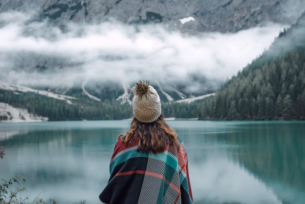 Freedom of travel woman hiker in lago di braies surrounded by dolomite mountains, italy. hiking, travel and adventures.