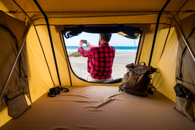 Freedom traveler man outside the tent in alternative vacation lifestyle in free camping at the beach taking picture of the natura landscape  backpack and camera inside and blue sea horizon surface