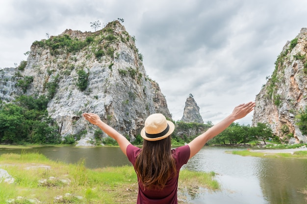 Freedom traveler woman in nature on mountain with raised arms enjoying happiness