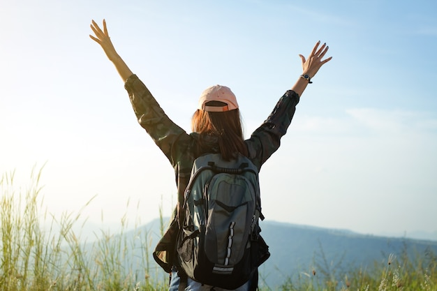 Freedom traveler woman standing with raised arms and enjoying a beautiful nature and cheering young
