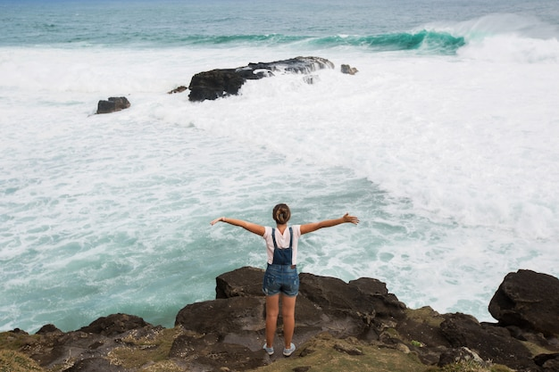 Freedom traveler woman standing with raised arms on the top of mountain and enjoy the beautiful of seascape. mauritius