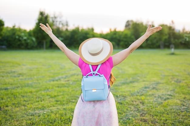 自由、勝利、成功のコンセプト-自由な幸せな女性が手を挙げた。後ろから見る。