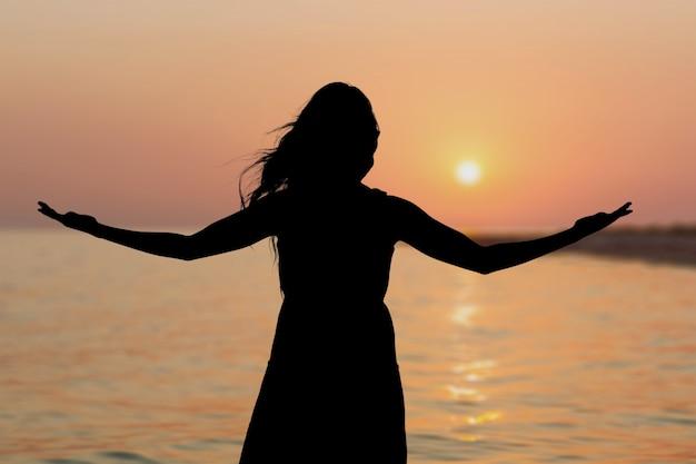 화창한 일몰에 해변에서 자유 여성이 행복하고 자유롭게 팔을 벌립니다.