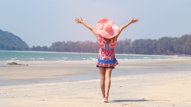Freedom woman standing arms outstretched back and enjoy life on the beach