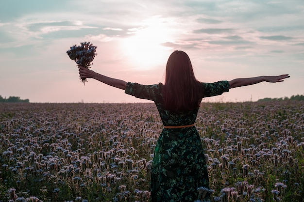 Freedom. woman with open arms and a bouquet of flowers at sunset on a flower meadow