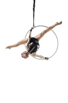 自由。若いアクロバット、白いスタジオの背景に分離されたサーカス選手。飛行中に完璧にバランスの取れたトレーニング、新体操アーティストが機器を使って練習します。パフォーマンスの優雅さ。 無料写真