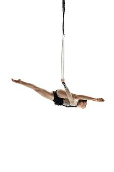 La libertà. giovane acrobata, atleta del circo isolato su sfondo bianco studio. allenamento perfetto equilibrato in volo, artista di ginnastica ritmica che si esercita con l'attrezzatura. grazia nelle prestazioni.