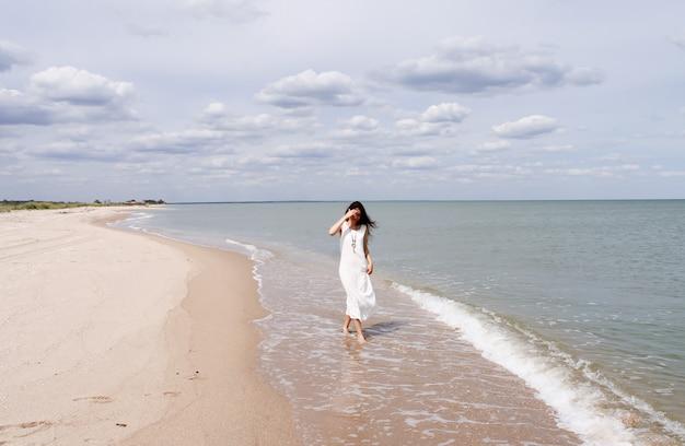 ビーチを歩く長い白いドレスを着て自由若い女性