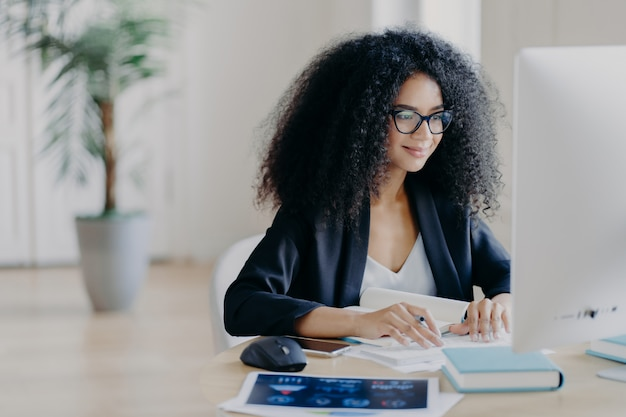 Freelance afro woman works remotely, writes information, focused at computer screen with delighted expression