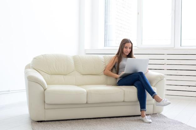 Концепция внештатных и людей - молодая женщина, сидящая на софе и работающая на ноутбуке.