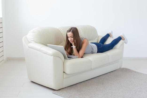 Концепция внештатных и людей - молодая женщина, работающая на ноутбуке дома