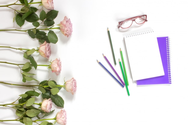 Freelance artist woman workspace. sketchbook, colored pencils, glasses and pastel pink roses on the desktop