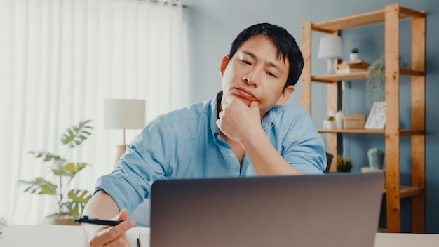 Freelance asia guy casual wear using laptop online in living room at home office.