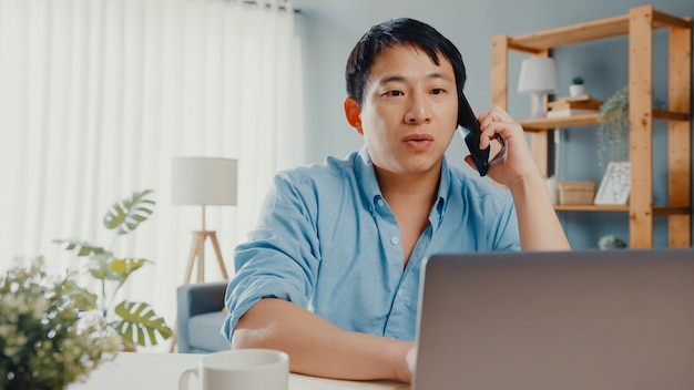 Freelance asia guy casual wear using laptop talk on cell phone in living room at house.
