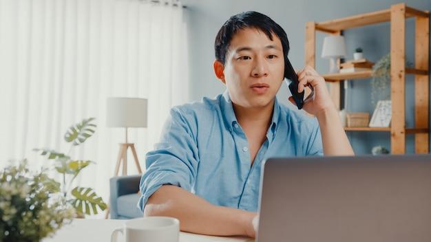 自宅の居間で携帯電話でノートパソコンの話を使ったフリーランスのアジア人カジュアルウェア。