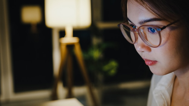 Signora asiatica indipendente che utilizza il duro lavoro del computer portatile nel soggiorno di casa.