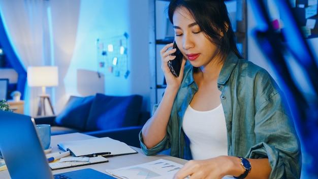 ノートパソコンを使用しているフリーランスのアジアの女性は、居間で遠く離れて働いている忙しい起業家に電話で話します。