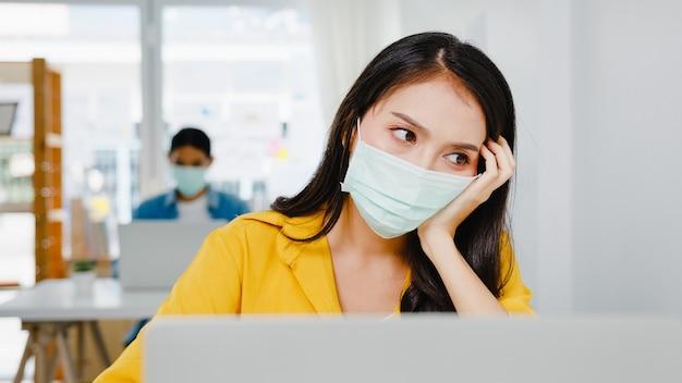 프리랜서 아시아 여성들은 새로운 일반 홈 오피스에서 노트북 열심히 일하는 얼굴 마스크를 착용합니다. 집 과부하, 자기 격리, 사회적 거리두기, 코로나 바이러스 예방을위한 격리 작업.