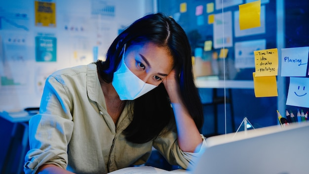 Freelance asia women wear face mask using laptop hard work at new normal office. working from home overload at night, self isolation, social distancing, quarantine for corona virus prevention.