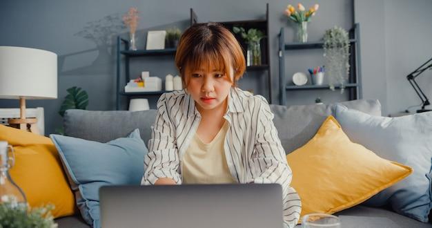 家の居間でラップトップオンライン学習を使用してフリーランスのアジアの女性のカジュアルウェア