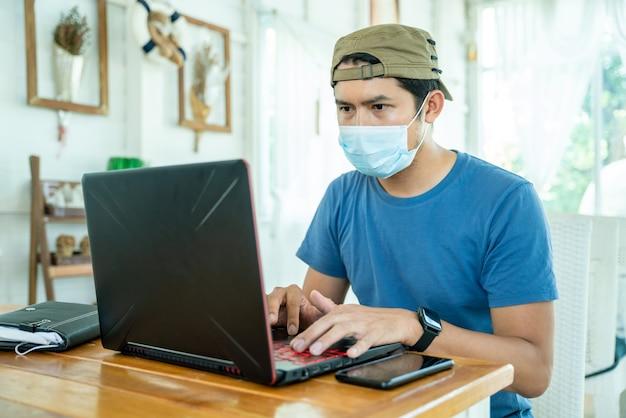 코로나 바이러스 또는 covid-19의 확산을 방지하기 위해 커피 숍에서 노트북으로 작업하는 얼굴 마스크를 쓰고 셔츠를 입은 프리랜서 아시아 사람