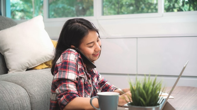 Freelance asian woman working at home, business female working on laptop and using mobile phone talking with customer on sofa in living room at home.