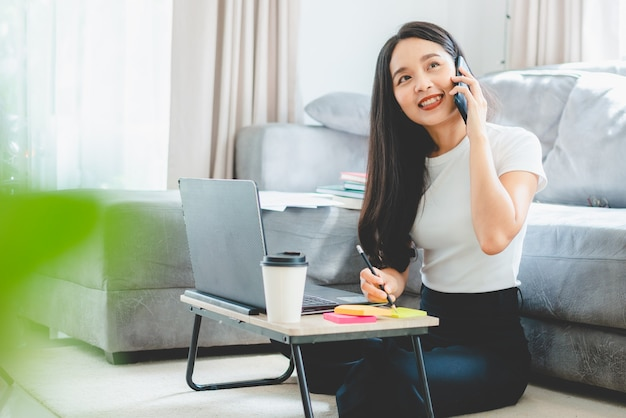 Freelance business woman working at home in the morning with laptop and hot drink cup, young happy female, businesswoman lifestyle computer technology online work