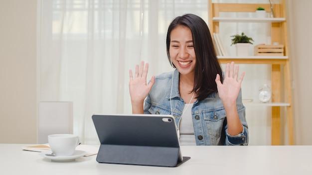 Носить независимых бизнес-леди вскользь используя видео-конференцию звонка таблетки работая с клиентом в рабочем месте в живущей комнате дома. счастливая молодая азиатская девушка ослабляет сидеть на столе делает работу в интернете.