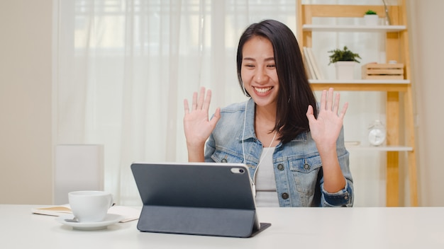 Freelance business women casual wear using tablet working call video conference with customer in workplace in living room at home. happy young asian girl relax sitting on desk do job in internet.