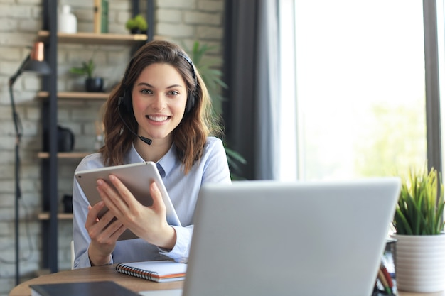 Freelance business women using tablet working call video conference with customer in workplace at home.