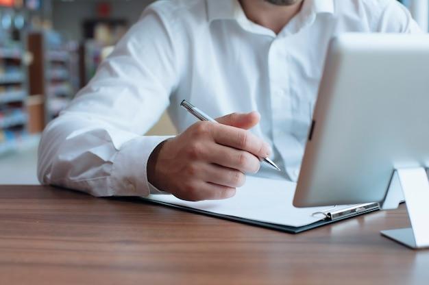 그의 손에 펜으로 흰 셔츠에 프리랜서 사업가 카페에서 계약에 서명