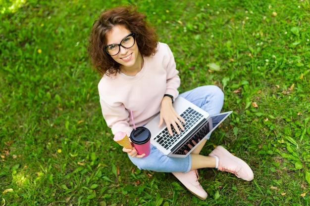 프리랜서 개념. 휴대용 퍼스널 컴퓨터와 커피 잔디에 앉아 여자