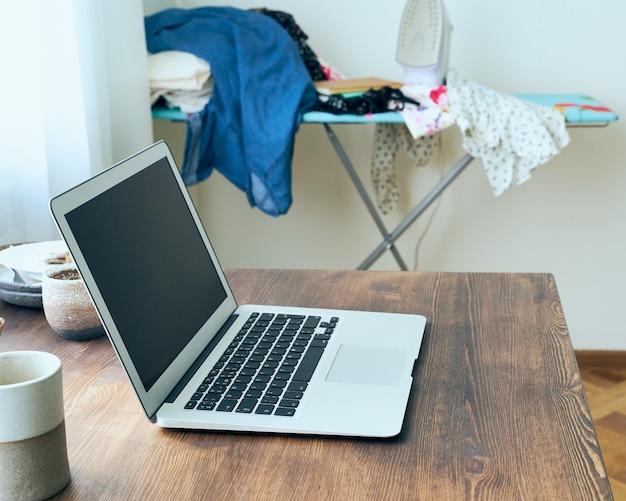 Стол фрилансера с ноутбуком в беспорядке в домашней квартире. карантин, самоизоляция, социофобия