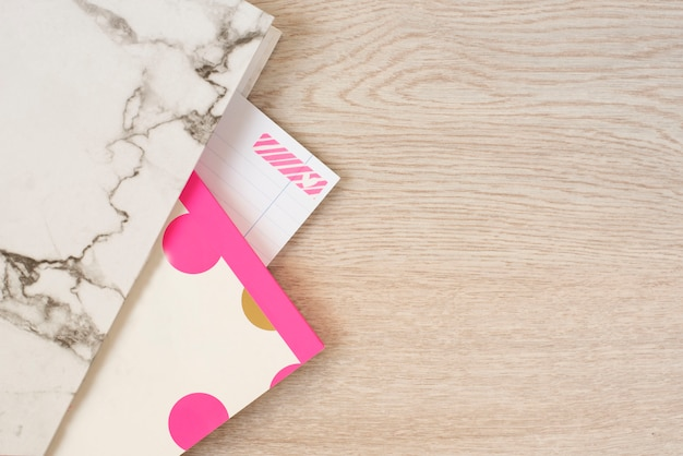 Freelance fashion femininity workspace in flat lay style marble folder, notebook, pink neon stationery on gray wooden