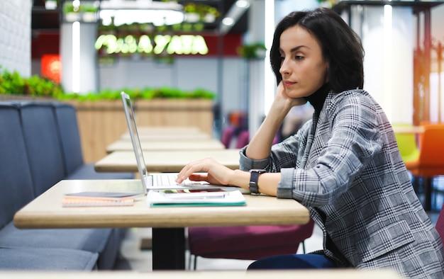 フリーランスの天国。公共の場に座ってノートパソコンで入力するスマートな衣装で忙しい女の子のクローズアップ写真。