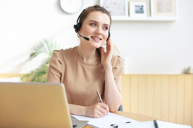 Оператор-фрилансер разговаривает с гарнитурой и консультирует клиентов из домашнего офиса.