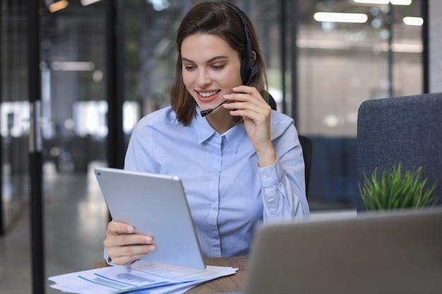 Оператор-фрилансер разговаривает с гарнитурой и консультирует клиентов из офиса.