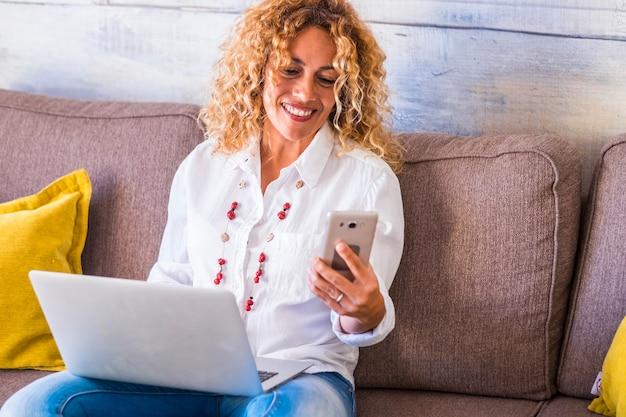 집에서 직장에서 프리랜서 사람들-아름 다운 성인 백인 여자는 전화 장치 및 노트북 컴퓨터 작동-개념 소파에 앉아. 독립적 인 여성을위한 비즈니스