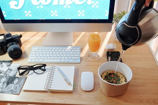 デスクで昼食をとっているフリーの写真家