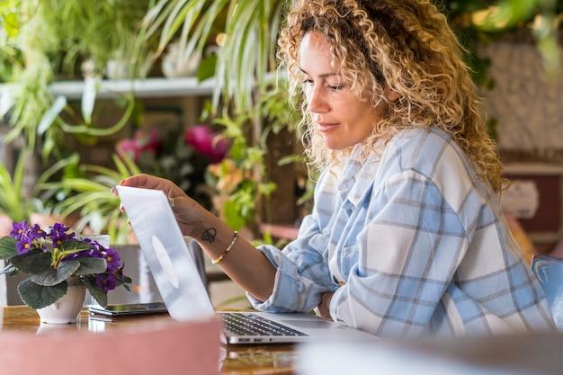 自宅のテーブルに座っているスマートな作業活動またはコワーキングストア活動のフリーランスのリモートワーカーの大人の女性-現代のオンライン仕事の人々とインターネット技術-美しい女性