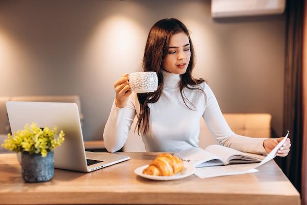 Внештатный студент молодой девушки с помощью ноутбука, сидя дома. молодая женщина сидит на кухне и работает онлайн на ноутбуке. довольно женщина пьет кофе чая во время работы.