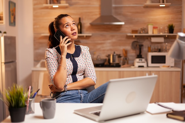 自宅のキッチンから深夜にクライアントと電話で取材しているフリーランスの女性。深夜に最新のテクノロジーを使用して、仕事、ビジネス、キャリア、ネットワーク、ライフスタイルのために残業している従業員。