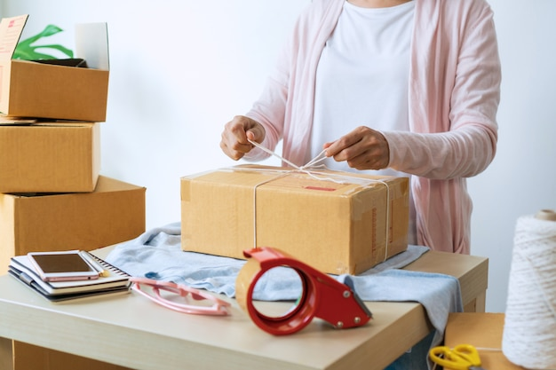 Внештатная женщина готовит картонные коробки для доставки клиенту